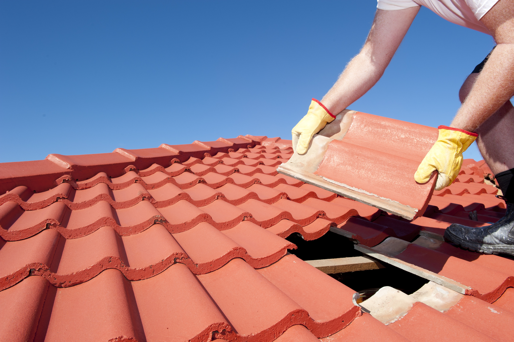 Roofing contractors applying shingles onto roof